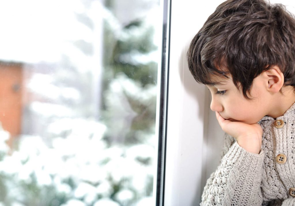 Christmas for foster children: young boy looking at window at snowy scene