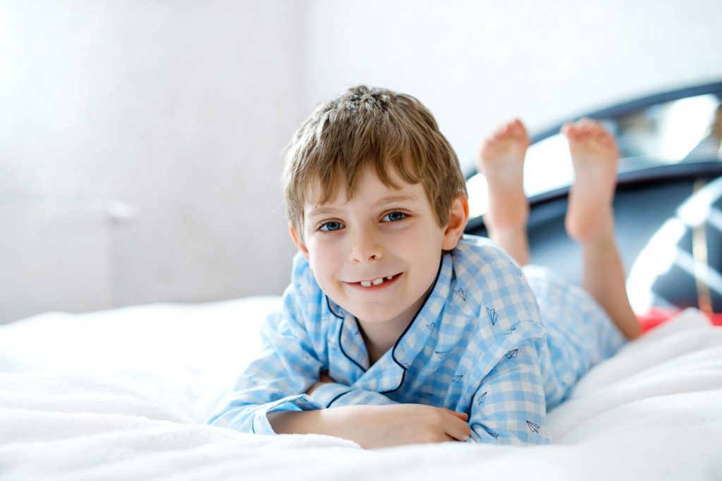 Spare room for fostering: young boy in pyjamas lying on bed